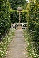 View down path leading to the stone sundial at York Gate Garden, Leeds, Yorkshire, UK.