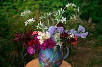 Sweet peas Lathyrus odoratus in a vase with Eryngium 'Silver Ghost' and 