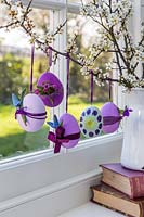 Decorated Easter eggs hanging on branches in windowsill