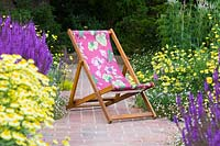 Deck chair with plants perfect for pollination - Anthemis tinctoria 'E.C. Buxton' Dyer's Chamomile AGM and Salvia nemorosa 'Amethyst' Balkan Clary, Erigeron karvinskianus
