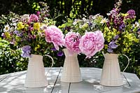 Mixed garden flowers arranged in white enamel jugs on table. Cut flowers include