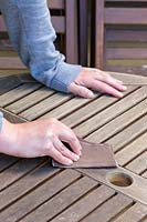 Woman sanding down surface of wooden garden table