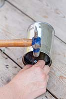 Using nail and hammer to make hole in tin can for fixing handle