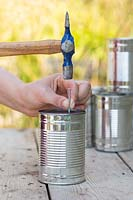 Using nail and hammer to make drainage hole in tin can