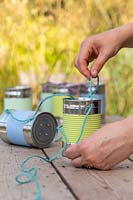 Threading string through holes in tin cans