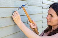 Hammering nail into wooden shed