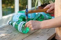 Using a counter sink and hammer to make hole in plastic bottle for string handle