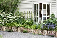 Raised border edged with logs planted with white foxgloves, viburnum, epimediums, ferns and fig - RHS Chelsea Flower Show 2018