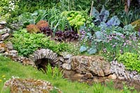 Welcome to Yorkshire Garden - Stream with stone bridge, Water Avens - Geum rivale 'Album', salad crops, Strawberries - Fragaria vesca, Leeks , Cabbages, Chives - Allium schoenoprasum and Sweet Peas Lathyrus sp. - Sponsor: Welcome to Yorkshire - RHS Chelsea Flower Show 2018