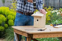 Using electric screwdriver to fix roof to bird box