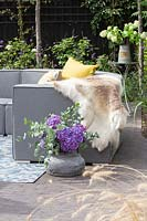 Grey outdoor sofa arrangement with yellow cushions, skin, tables, drinks and floral arrangements