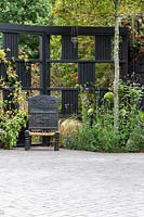 Black trellis room divider and decorative chair and mixed planting
