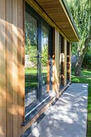 Wood clad Summerhouse with large glass doors and windows set among mature trees