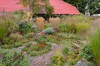 Sunken centre of bed with herbaceous perennials and grasses
