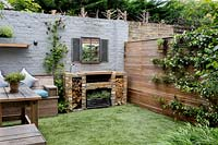Courtyard garden in West London with artificial lawn, brick barbecue and Cedar battened Trellis