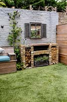 Small courtyard garden in West London with artificial lawn and brick barbecue