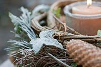 An Advent wreath on a table in the garden bonded out of Pinus strobus cones, 