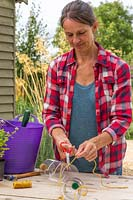 Woman using scissors to cut the garden string to the right length