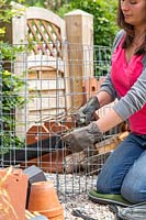 Woman creating the gabion cage by wiring the corners