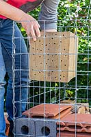 Woman adding wood block with holes into wire cage