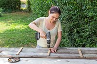 Fixing together two long boards with small cross timbers using electric screwdriver
