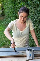 Woman painting the long boards grey using a paint brush