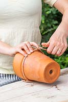 Twisting copper wire around a terracotta pot to enable the pot to hang from the wire loop