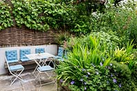Patio area in Large house in North London with seats and table Geranium 'Rosanne',