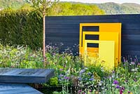 Yellow steel sculptural panels with black fence and meadow-style planting. 'Urban Oasis', RHS Malvern Spring Festival 2018.