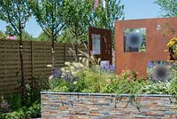 Fence with row of Prunus serrula, raised bed with tile feature and steel decorative panels by Steel Project Management - RNIB's Community Garden, RHS Hampton Court Palace Flower Show 2018