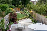 High view of contemporary garden with wood deck patio and artificial lawn.