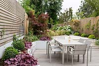 View of wooden decking and stone patio with garden furniture in modern garden.
