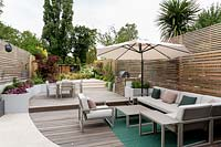 View of curved wooden decking and stone patio with garden furniture and parasol in contemporary garden.