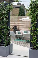 Wood fencing, wood deck patio with parasol and garden chairs Contemporary garden in Dulwich