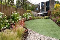 View down modern garden with artificial grass and flowering shrubs.