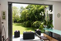 View to patio and garden from inside house through open bifold doors.