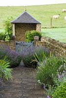 Path with lavender and gate with pavilion in farmland. Dorset, UK