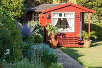 View of painted summerhouse in coastal garden.