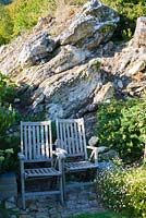 Wooden chairs set against rock outcrop surrounded by rosemary, sedums and wall daisy, Erigeron karvinskianus.