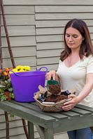 Woman adding compost to basket lined with hessian and plastic prior to planting.