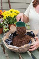 Adding compost to basket lined with hessian and plastic
