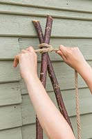 Tying together to long hazel sticks with rope