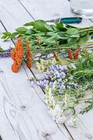 Ingredients for tying a mixed bouquet of garden flowers laid out on table.
