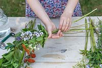Woman selecting flowers and tying a bouquet.
