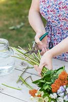 Using secateurs to cut ends from flower stems to ensure even length