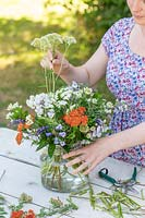 Woman adding stems of flowers to bouquet in glass vase.