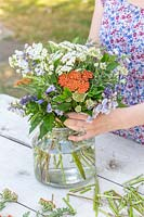 Woman arranging stems of flowers in bouquet in glass vase.