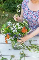 Adding stems to bouquet in glass vase