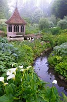 Summerhouse in the bog garden by a stream fringed with moisture loving plants. The Old Rectory, Netherbury, UK.