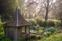 Summerhouse beside a bog garden with avenue of clipped Yew pyramids beyond.